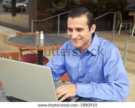 Handsome hispanic businessman surfing the internet on a laptop. #5880910