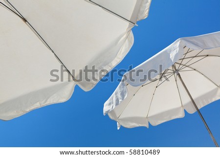 White beach umbrellas against a blue sky in the French Riviera in Nice, France. #58810489