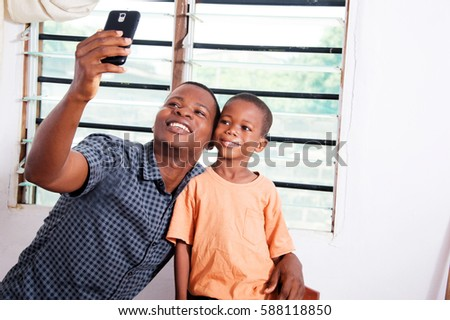 Father and son are very happy to take pictures with his mobile phone. #588118850