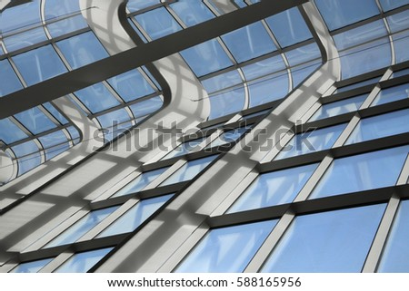 Reworked photo of transparent wall. Public / office building interior fragment with curvilinear shapes. Glazed aluminum structures. Modern glass architecture with reflections and shadows. #588165956