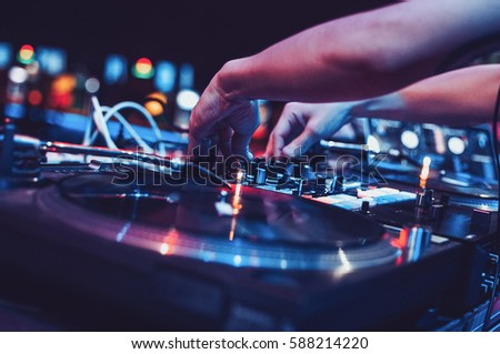 MOSCOW-2 MAY,2016:Party dj mix music tracks on edm festival in night club.Hands of disc jockey mixing musical set on sound mixer controller in nightclub.Professional turntables sound system #588214220