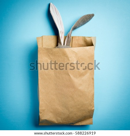 Easter bunny in a paper bag. Rabbit. Blue background. Space for text. Black lettering happy easter.