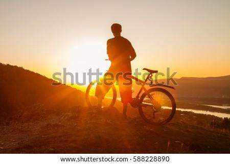 Biker resting while watching sunset #588228890