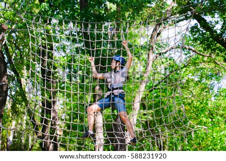 adventure climbing high wire park - people on course in mountain helmet and safety equipment #588231920