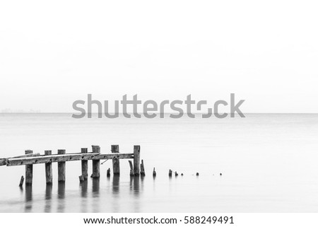 Seascape tranquil background with room for text, rustic pier posts in lower left of water #588249491