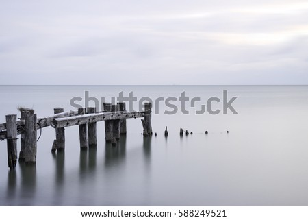 Posts of a broken pier leading out into calm blue tranquil sea water #588249521