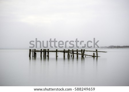 Broken pier in calm tranquil water, posts reflecting with misty foggy background seascape #588249659