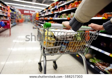 London, UK - August 18, 2014: A shopper pushes a trolley along an aisle in an Asda supermarket. American company Walmart owns Asda, which is UK's largest retail chain after Tesco with 568 stores. #588257303