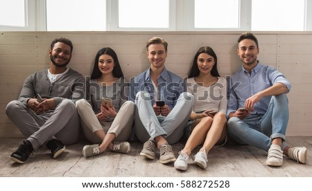 Group of beautiful young people in casual clothes using smartphones, looking at camera and smiling while sitting together on the floor #588272528