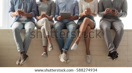 Cropped image of beautiful young people in casual clothes using gadgets while sitting together on the window sill #588274934