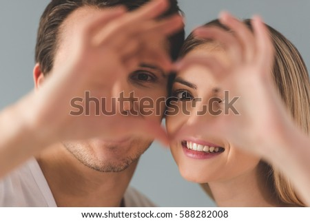 Beautiful young couple is making heart of their fingers and smiling, close-up #588282008