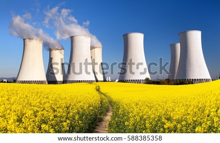 Panoramic view of Nuclear power plant Jaslovske Bohunice with golden flowering field of rapeseed, canola or colza - Slovakia - two possibility for production of electric energy Royalty-Free Stock Photo #588385358