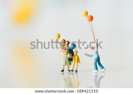Miniature people with balloon using as background family or happy concept.. #588421310