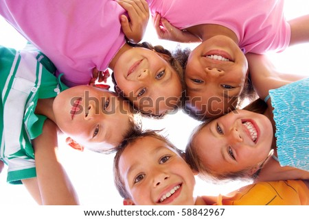 Below view of happy children embracing each other and smiling at camera #58842967