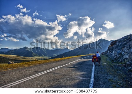 Altai mountain road. Chuysky Tract. In the background the mountains. The photo was taken during a cycling trip through the Altai in the summer in August. Russia. Away goes the cyclist on the bike. #588437795