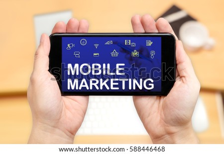 Watching two hand holding mobile phone with Mobile marketing word on screen and blur desk office background,Digital content concept #588446468