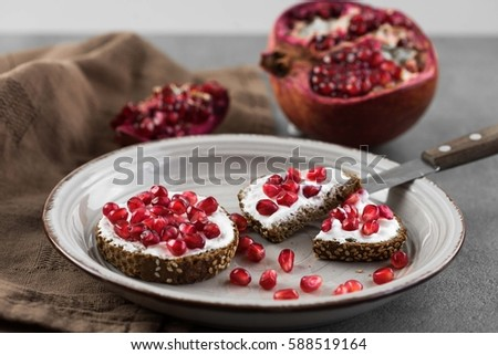 bread with cream cheese and pomegranate seeds. #588519164