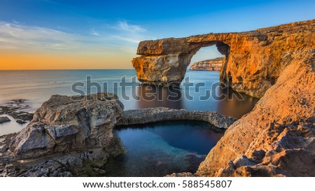 Gozo, Malta - The beautiful Azure Window, a natural arch and famous landmark on the island of Gozo at sunset Royalty-Free Stock Photo #588545807