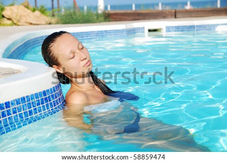 Young beautiful woman having rest in swimming-pool #58859474