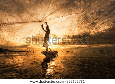 Silhouette Fisherman Fishing Nets on the boat.Thailand Royalty-Free Stock Photo #588625781