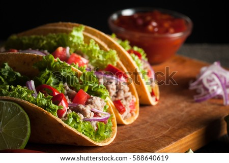 Photo of Mexican tacos with ground beef, onion, tomatoes, chili, red sauce, lettuce and lime on wooden background. Spicy and fast food concept. #588640619