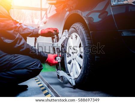 Car mechanic installing sensor during suspension adjustment. Wheel alignment work at repair service station Royalty-Free Stock Photo #588697349