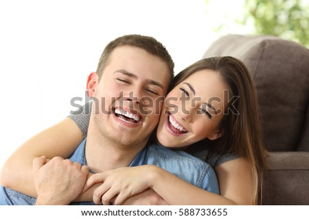 Happy couple with perfect white smile posing and looking at camera on a couch at home #588733655