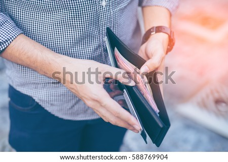 Man standing holding black wallet full of money Royalty-Free Stock Photo #588769904