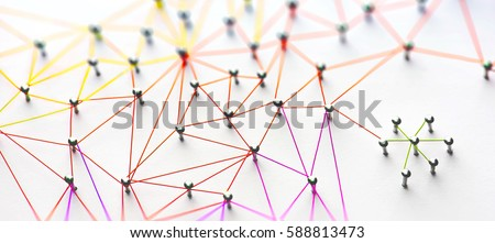 Linking entities. Networking, social media, SNS, internet communication abstract. Small network connected to a larger network. Web of red, orange and yellow wires on white background. Shallow DOF.  Royalty-Free Stock Photo #588813473
