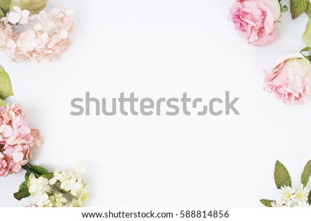 Frame made of pink and beige roses, green leaves, branches on white background. Flat lay, top view. Wedding's background