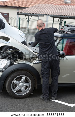 Automobile glazier worker disassembling windshield of a car #588821663