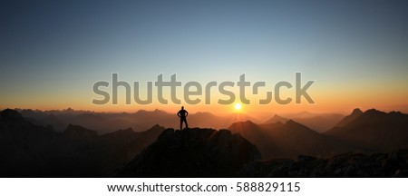 Man reaching summit enjoying freedom and looking towards mountains sunset. Royalty-Free Stock Photo #588829115