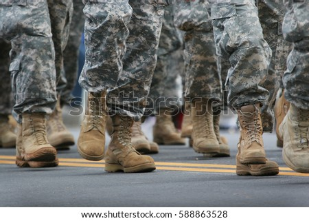 Soldiers dressed in army camouflage in an army parade  Royalty-Free Stock Photo #588863528