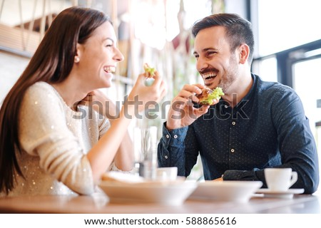 Happy loving couple enjoying breakfast in a cafe. Love, dating, food, lifestyle #588865616