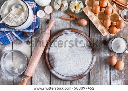 Baking background. Cooking ingredients for dough and pastry making and sprinkled with flour pizza board on rustic wood. Top view with copy space, mockup for menu, recipe or culinary classes. Royalty-Free Stock Photo #588897452