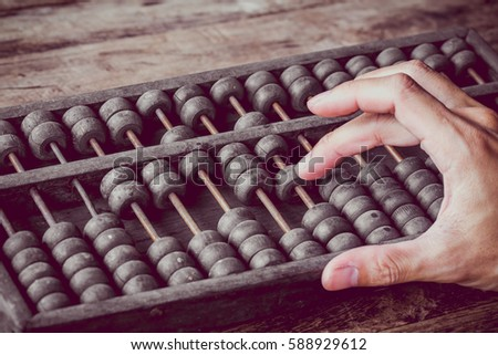 Vintage tone of Man's hands accounting with old abacus and hold electronic calculator. picture financial concept design.