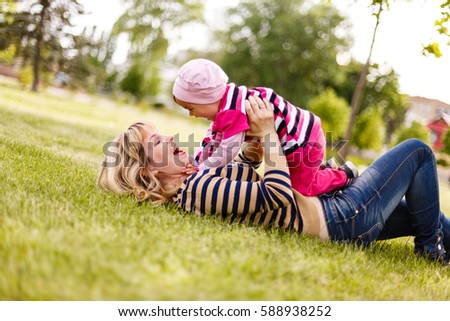 mother and daughter lie on the grass laughing #588938252