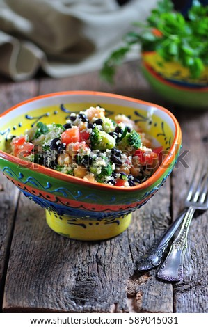 Healthy salad of chickpeas, couscous, black beans with tomato, broccoli, parsley, olive oil and sea salt. #589045031