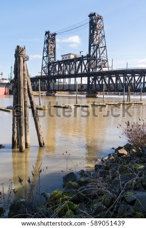 Portland, Oregon - February 25, 2017 - Freight Train Traveling Under a Bridge Going Across the Steel Bridge Willamette River. #589051439