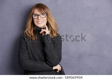 Shot of a beautiful mid adult woman smiling on gray background. Royalty-Free Stock Photo #589069904