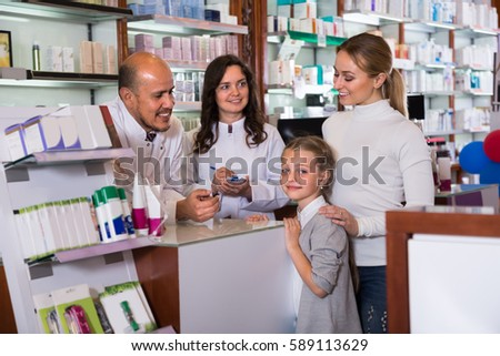 Two friendly smiling pharmacists in white coats standing at the counter and consulting a customer with child. Selective focus  #589113629