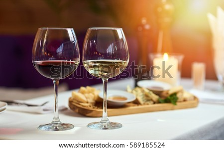 Two glasses of wine white and red standing on a table with candle in the sun light  #589185524