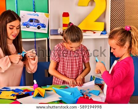 Paper craft work for children. Dreams flight of child in kindergarten. Happy boy child playing with origami airplane in kindergartener or school. #589194998