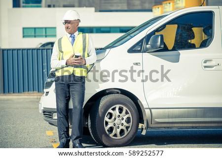 Senior engineer man in suit and helmet outdoor having coffee #589252577