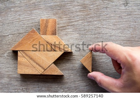 Wooden tangram puzzle wait to fulfill home shape for build dream home, happy life, house or mortgage investment concept Royalty-Free Stock Photo #589257140