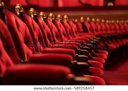 Traditional classically regal ornate rounded wood armed formal plush deep red velvet opera movie theater chairs in curved row with decorative gold molding in fancy carpeted venue Royalty-Free Stock Photo #589258457