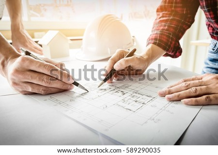 Architects engineer discussing at the table with blueprint - Closeup on hands and project print Royalty-Free Stock Photo #589290035