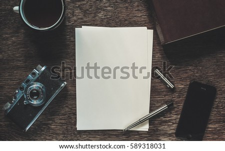 Writing a letter. Sheets of paper, pen, retro camera, cup of tea, smart phone and book on wooden table, top view.