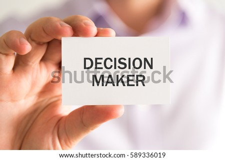 Closeup on businessman holding a card with DECISION MAKER message, business concept image with soft focus background and vintage tone