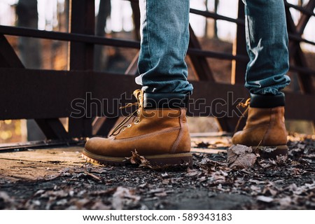 man wearing boots standing on bridge Royalty-Free Stock Photo #589343183